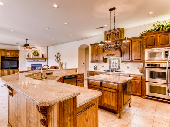 Gorgeous chef's kitchen with gas cooktop & double oven, overlooks wall of windows to backyard & den with stone fireplace.